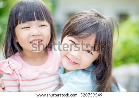 two little girls smile happily in the park,asian