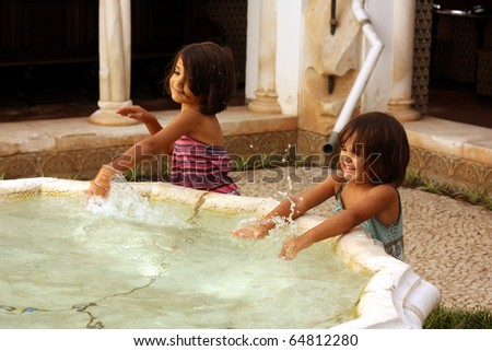 Two little girls smiling and playing outdoors with water from a fountain - stock photo