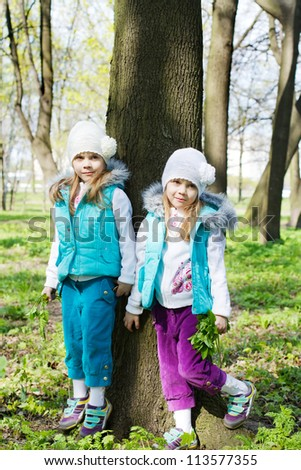 two little girls stand at a tree - stock photo