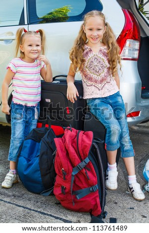 two little girls standing near the car with backpacks - stock photo