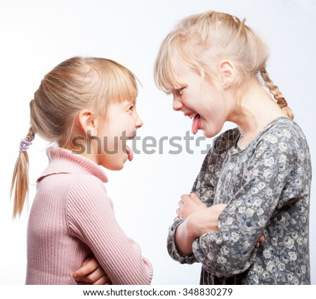 Two little girls stick out tongues teasing each other - stock photo