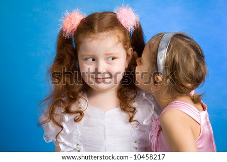Two little girls talking in whispers - stock photo
