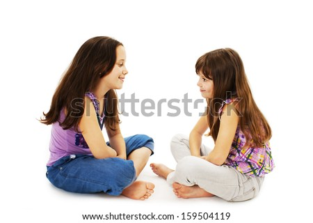 Two little girls talking. Isolated on white background  - stock photo