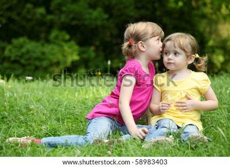 Two little girls telling secrets, outdoor - stock photo