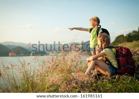 two little girls watching the sunset on the lake - stock photo