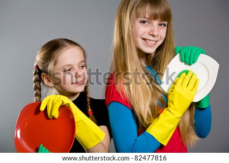 Two little girls wearing rubber gloves holding plates - stock photo