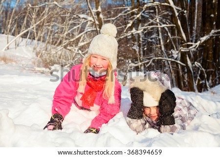 Two little girls wearing winter clothing having fun playing in a fresh snow outdoors - stock photo