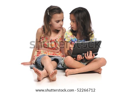 Two little girls with a laptop computer isolated on a white background - stock photo