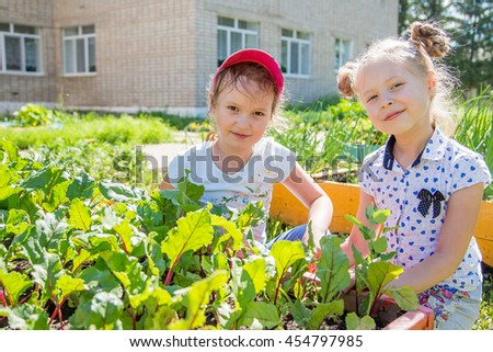 two little girls with a smile help with the work of gardening