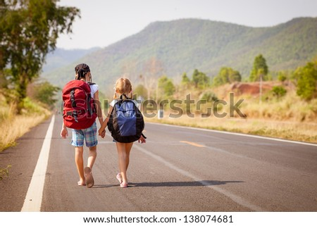 two little girls with backpack walking on the road - stock photo