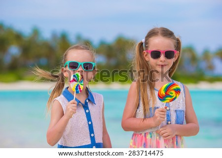 Two little girls with bright tasty lollipops on white beach  - stock photo