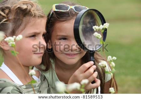 Two little girls with magnifying glasses - stock photo