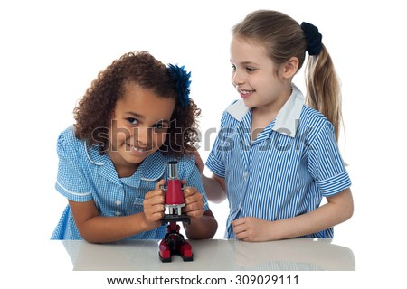Two little girls with microscope in classroom - stock photo