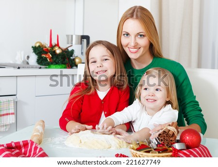 Two little girls with mother baking Christmas cookies in the kitchen - stock photo