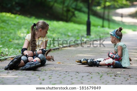 Two little girls with roller blade at park - stock photo
