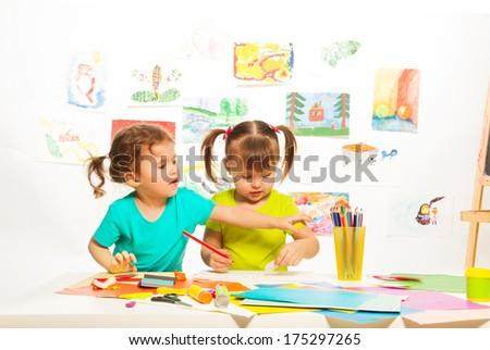 Two little happy girls painting on creative class in kindergarten - stock photo