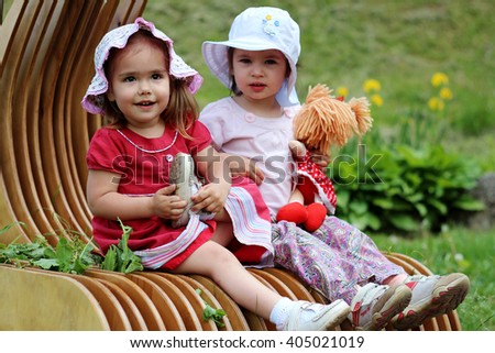 Two little happy smiling girl friends in summer dresses and with doll have a fun on the bench in the meadow, playing outdoors in spring park, summer and spring outdoors - stock photo