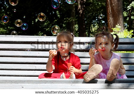 Two little happy smiling girl friends on the bench in the park blowing soap bubbles and having fun, summer and spring outdoors - stock photo