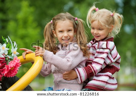 two little joyful little girls on the playground in park