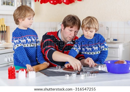 Two little kid boys and dad baking gingerbread cookies. Happy siblings, children in blue xmas pullovers. Kitchen decorated for Christmas. Family, holiday, kids lifestyle concept.