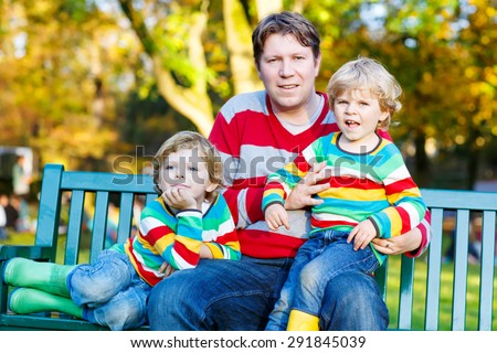 Two little kid boys and young father sitting together in colorful clothing. Happy siblings and their dad having fun in autumn park on warm day. - stock photo