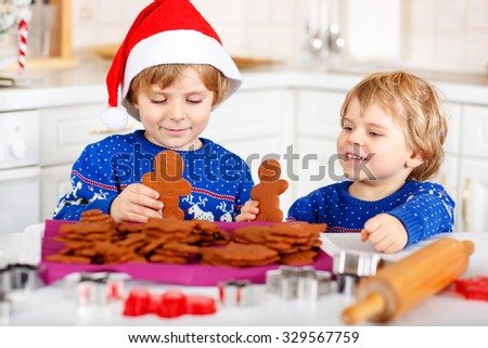 Two little kid boys baking gingerbread cookies. Happy siblings, children in blue xmas pullovers. Kitchen decorated for Christmas. Family, holiday, kids lifestyle conceplt. - stock photo