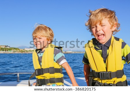 two little kid boys, best friends enjoying sailing boat trip. Family vacations on ocean or sea on sunny day. Children smiling. - stock photo