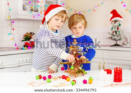 Two little kid boys decorating selfmade Christmas tree. Happy siblings, children in xmas pullovers. Kitchen decorated for Christmas. Family, holiday, kids lifestyle concept. - stock photo