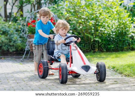 Two little kid boys having fun with toy race car in summer garden, outdoors. Adorable brother pushing the car with younger child. Outdoor games for children in summer concept. - stock photo