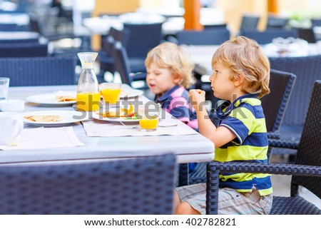Two little kid boys having healthy breakfast in hotel restaurant or city cafe. Funny children eating vegetables and drinking juice Selective focus. - stock photo