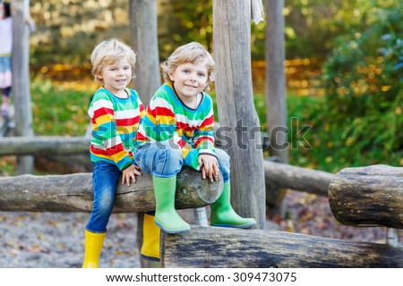 Two little kid boys in colorful shirts with stripes and gumboots having fun with playing on playground on warm, autumn day, outdoors. Family, happy childhood,  kids concept - stock photo
