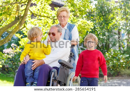 Two little kid boys, their grandmother and grandfather in wheelchair in summer garden. Happy family spending time together. - stock photo