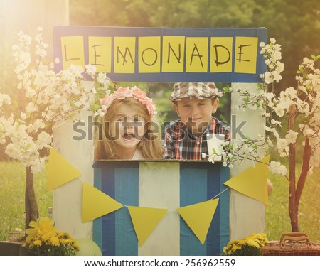 Two little kids are selling lemonade at a homemade lemonade stand on a sunny day with a sign for an entrepreneur concept. - stock photo