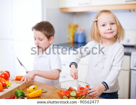Two little kids at kitchen making salad - stock photo
