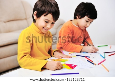 Two little kids at the table draw with crayons - stock photo
