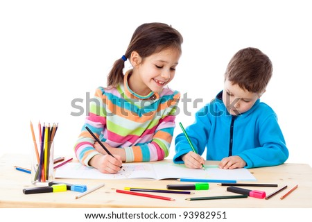 Two little kids at the table draw with crayons, isolated on white