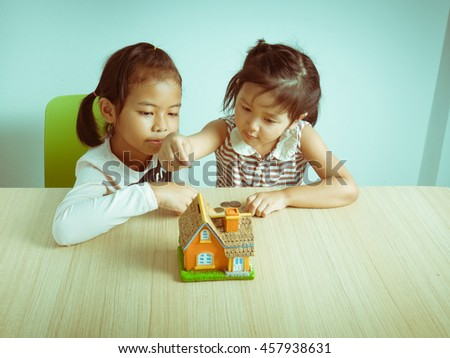 Two little kids at the table with house piggy bank