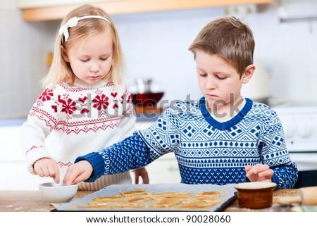 Two little kids baking Christmas cookies - stock photo