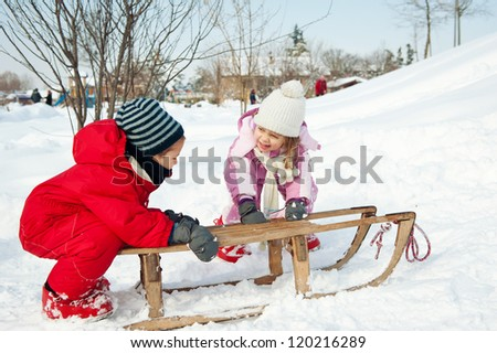 Two little kids - boy and girl - having fun with sled in the snow. - stock photo