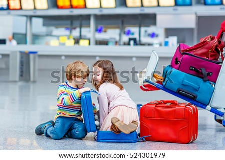 Two little kids, boy and girl with suitcases at the airport, indoors and waiting for family vacations. Happy children, twins, brother and sister exciting about air travel trip and flying with airplane