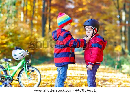 Two little kids boys, best friends in autumn park. Older brother helping younger child to put his bike helmet. Active siblings with bicycles. Happy family - stock photo