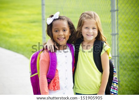 Two little kids going to school together - stock photo