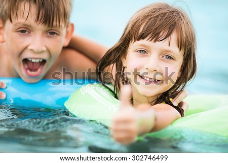 two little kids playing in the swimming pool - stock photo
