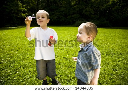 Two Little Kids Playing With Soap Bubbles - stock photo