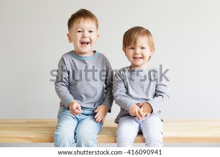 Two little kids. Portrait of a happy little children - boy and girl. Beautiful kids against a white background - stock photo