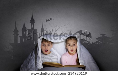 Two little kids reading book under blanket - stock photo