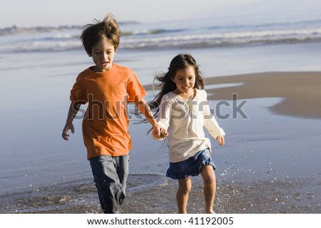 Two Little Kids Running Along the Water at The Beach - stock photo