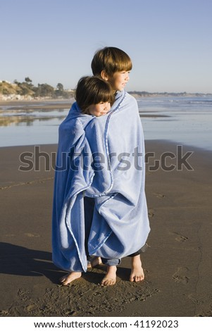 Two Little Kids Standing at Beach Wrapped in a Blanket Looking out to Sea