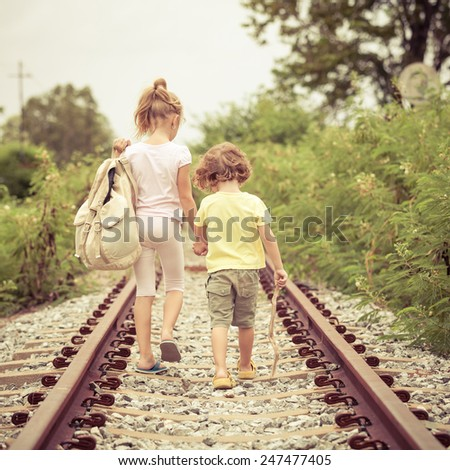 two little kids with backpack standing on the railway at the day time - stock photo