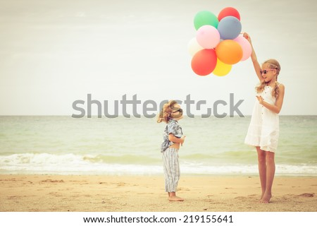 Two little kids with balloons standing on the beach at the day time - stock photo